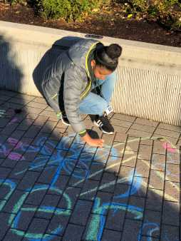 Behare Goshime '22 designing the walkway using chalk.