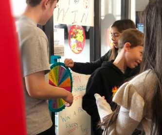 Paxton Wong '20 in charge of spin the wheel. Photo By Sita Alomran '19.