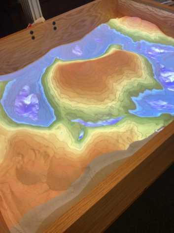 The augmented reality sandbox with the projector turned on. Photo by Michael Young '23.