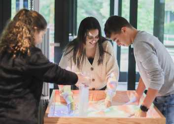 Talia Hammer, Sylvia Tejada, and Owen Williams '23 create a meandering river basin system with tributaries and deltas using the new Augmented Reality sandbox.