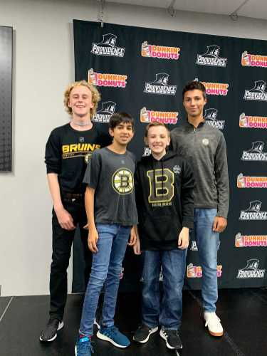 Brian Gamble, Nico Jaffer, Daniel Murray, and George Purdy, all '23, pose with their Bruins gear.