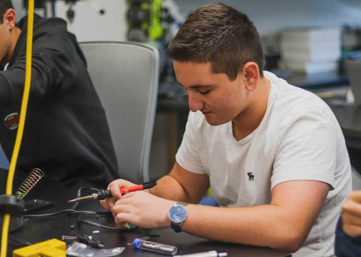 Joseph Bahaddy '21 uses solder to create a digital clock.