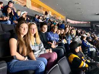 Haleigh Jacobs '23, Paige Gamble '24, Zakkai Mares van Praag '22, Neel Kumar '22, Brian Barrera '22, Catherine Leeder '20, Libby Foley '20, and Caroline Champa '20 watch the Providence Bruins play the Rochester Americans after singing on the ice.