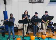 """Ugo Adiele '23, Dieter Gartner '22, Ray Park '22, and Simon Price '22 jam out to """"Funky Monkey"""" onstage."""