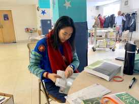 Yutong Zou '22 puts two books in an envelope at the Packing table. Photo by Edan Zinn '23.