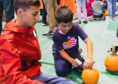 George Purdy '23 watches as his Lower School buddy hammers a toothpick into his pumpkin.