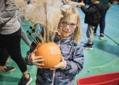 A Lower School student shows off her pumpkin.