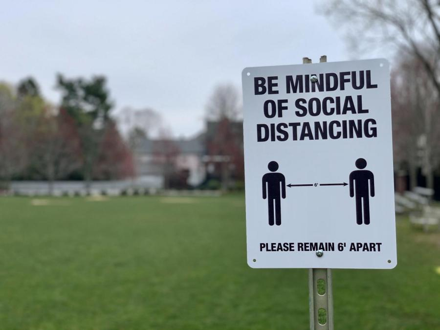 A sign on the Athletic Field reminding passerby to practice Social Distancing. Gator file photo.