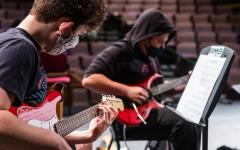 Kieran Cross '23 (front) and Jack Nathanson '23 play the guitar during a rehearsal.