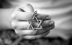 A person holds the Jewish Star of David, a symbol of the faith.