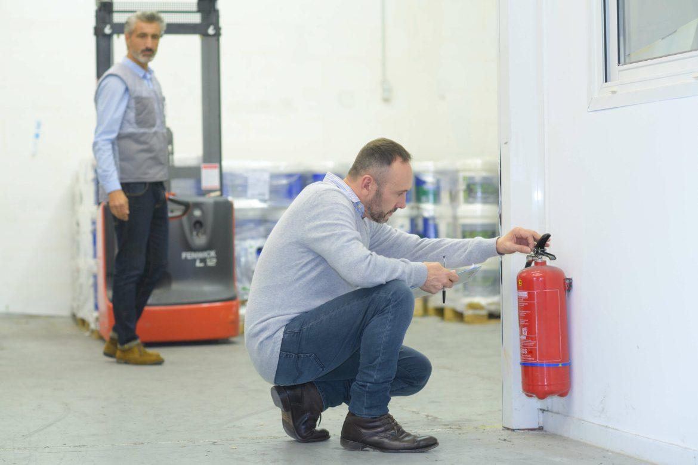 Mann überprüft Feuerlöscher