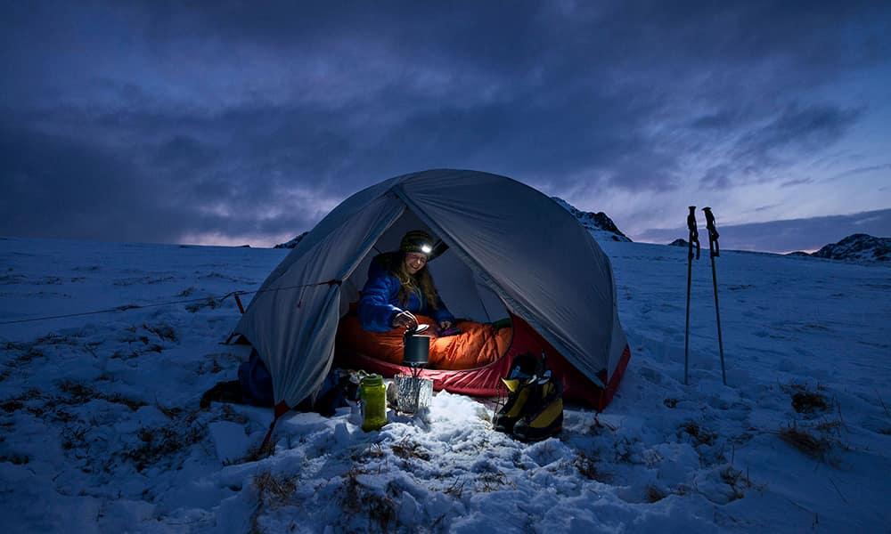 Теплая одежда и укрытие могут сыграть решающую роль в борьбе за жизнь в ситуации выживания. По этой причине даже любители похода выходного дня должны озаботиться такими предметами снаряжения, как послойная одежда, вода, еда и укрытие от непогоды. Женщина готовит завтрак в своей палатке во время кемпинга в Вествагойя, Лофотенские острова, Норвегия.