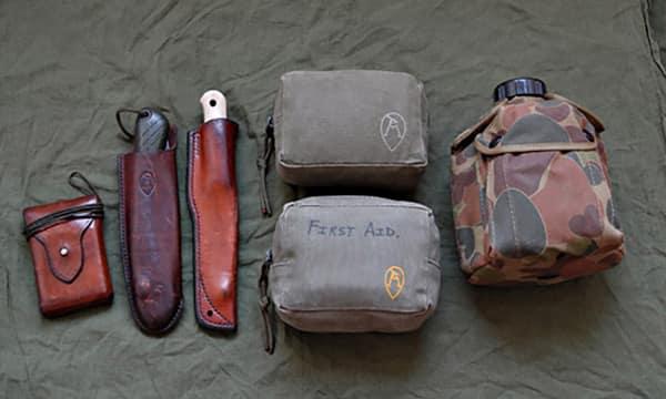 Пример набора для выживания в условиях дикой природы (слева направо): компас, складная пила, нож, НАЗ (верхняя сумка), индивидуальная аптечка для походов в пустыню (нижняя сумка), фляга для воды в комплекте с кружкой.