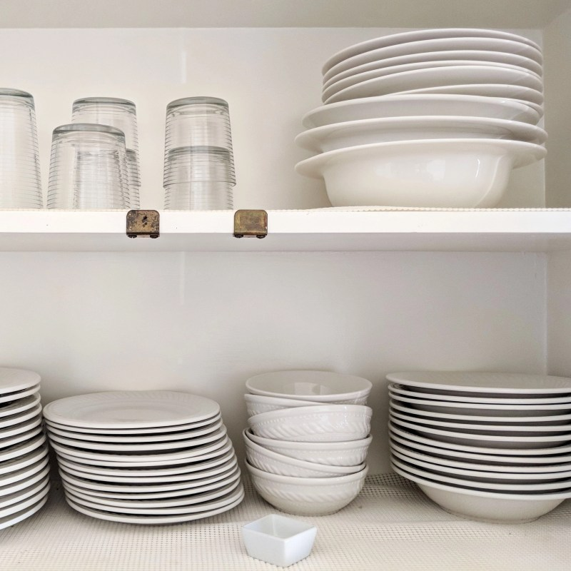 white dishes stacked in a cabinet