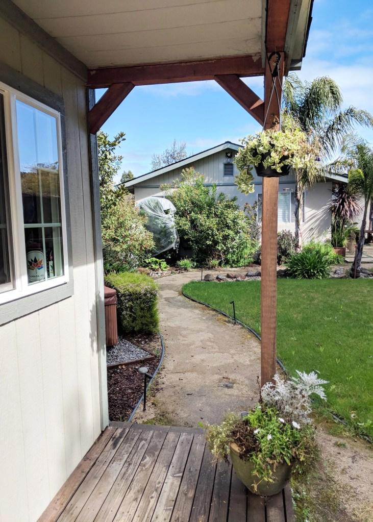 view off small porch towards sunny backyard