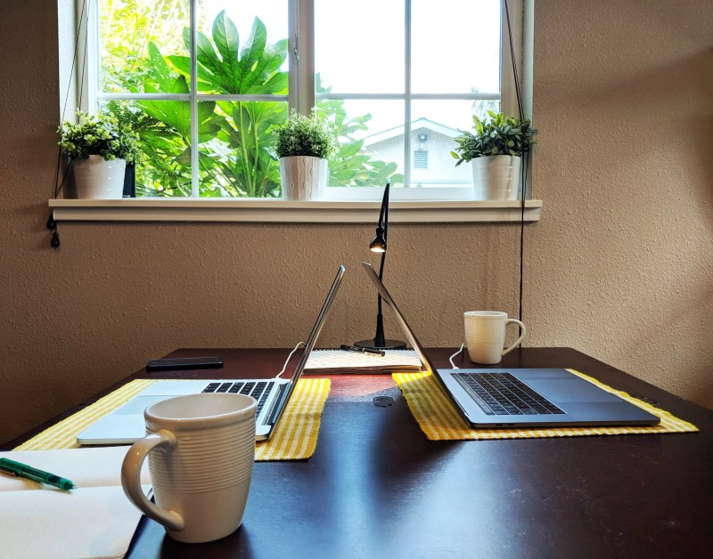table with two laptops and coffee cups