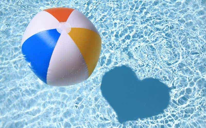 Beach ball floating on the surface of an inground swimming pool, casting a shadow in the shape of a heart
