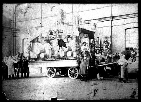 Brewery workers with beer barrels and hops on a carnival cart.