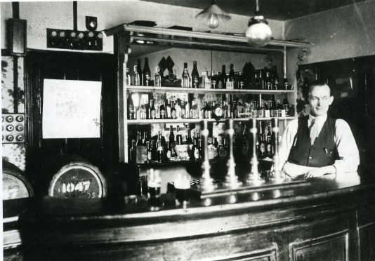 Mr Crinnion behind the bar, The Malting House Public House, Felling, 1930, from Gateshead Libraries photo archive.