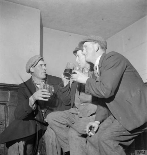 Three men talking and drinking beer.
