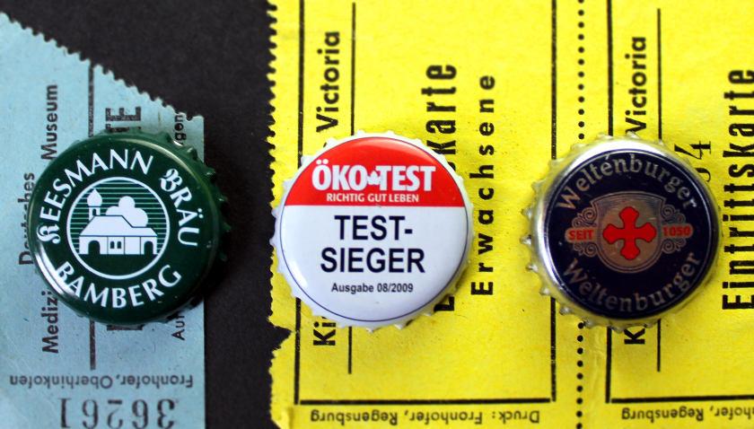 Three beer caps on old German ticket stubs.