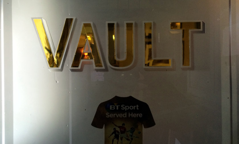 Sign on a frosted glass pub door: VAULT.