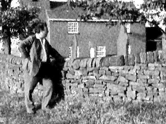 Ian Nairn leans on a wall.