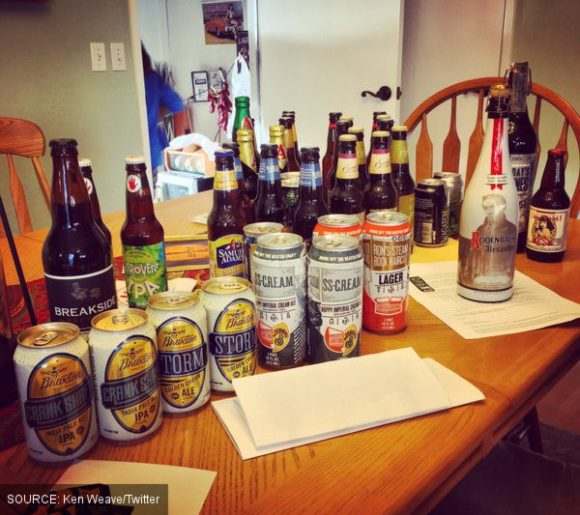 Many beers piled up on a table.