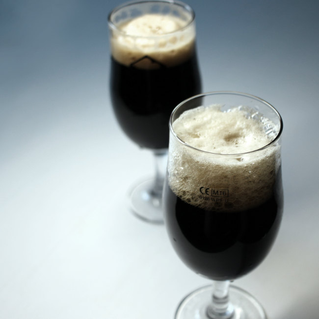 Two stouts, side by side, in stem glasses.