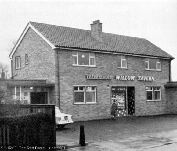 Exterior view of the Willow Tavern with man in mac and parked car.