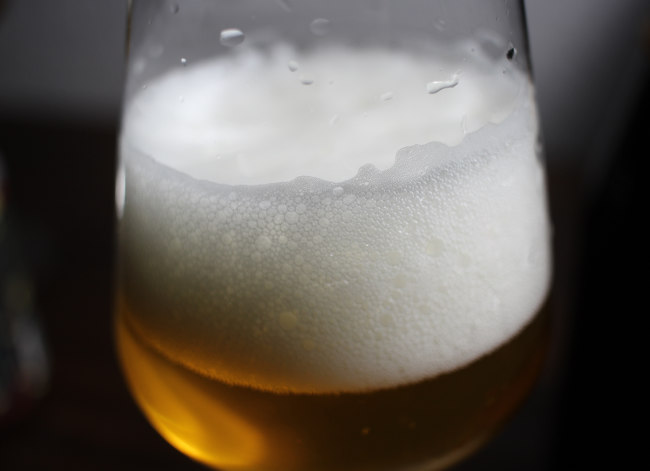The head of a glass of beer with glinting light.