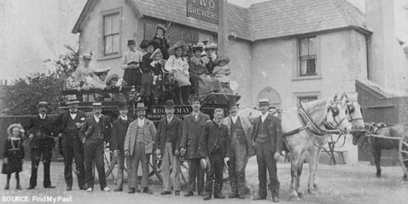A horse-drawn charabanc outside a pub.