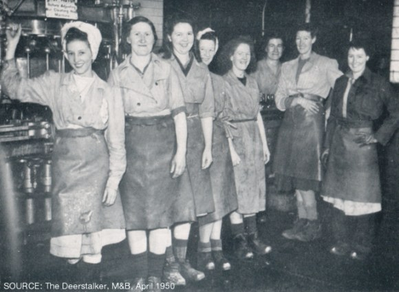 Women in work clothes smiling.