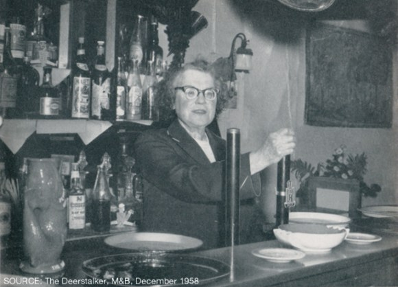A woman behind the beer pumps.
