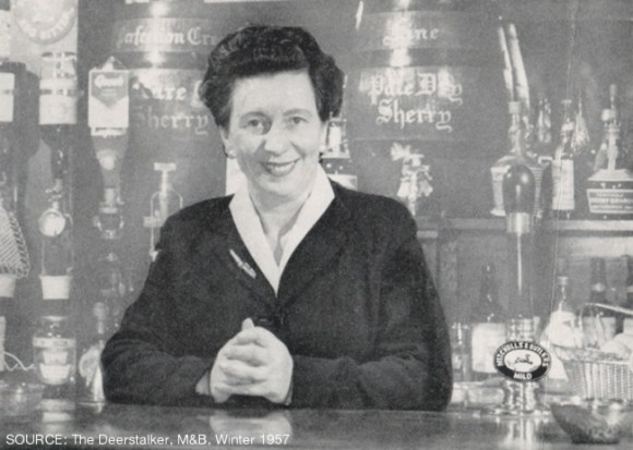 A posed photograph of a woman behind the bar at a pub.