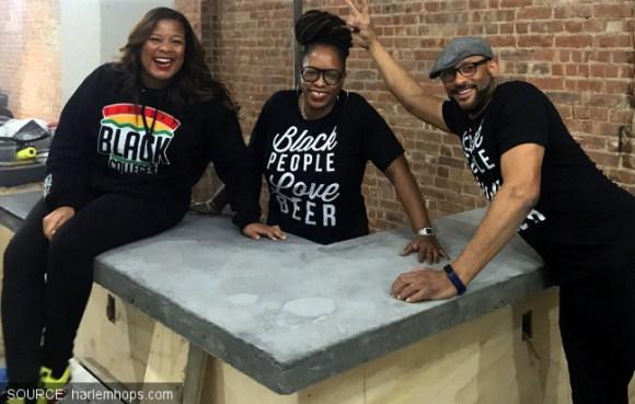 Three people posing by a half-built bar.