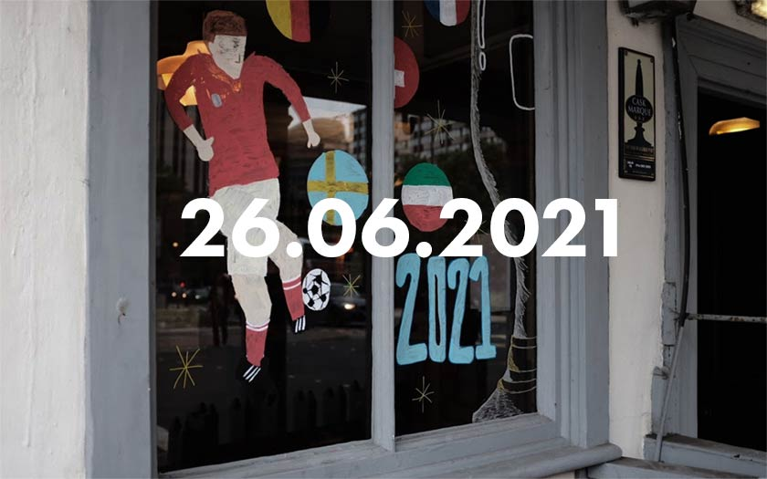 A pub window with a painted footballer and flags.