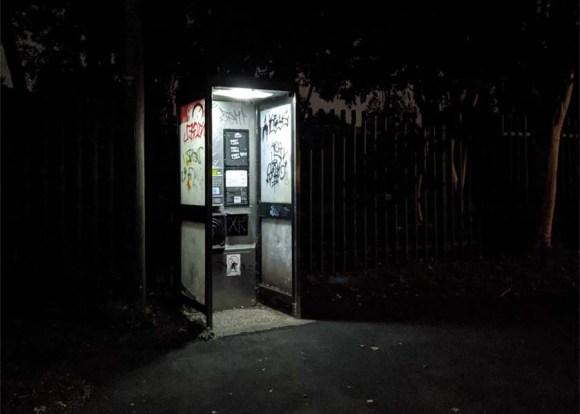 A vandalised phone box.