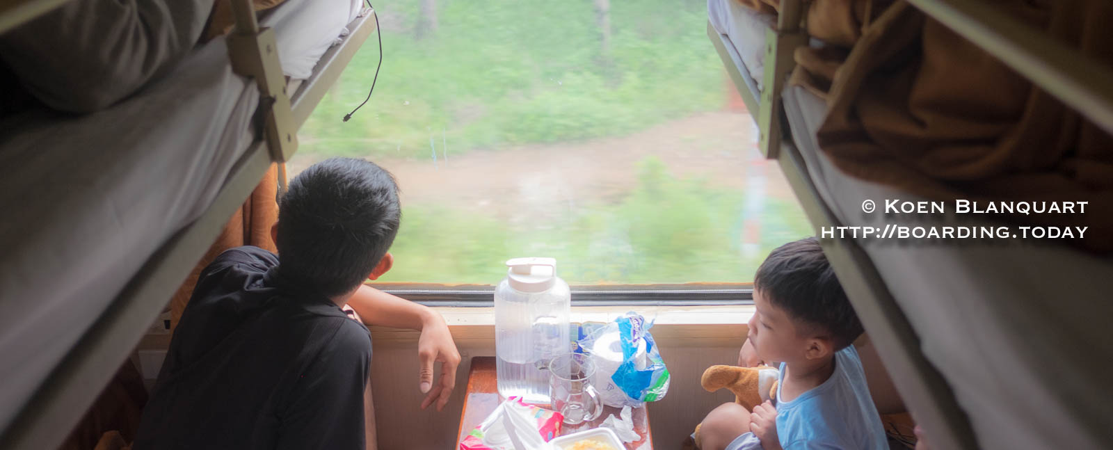 Father and son watching the changing landscape from the train saigon to hanoi