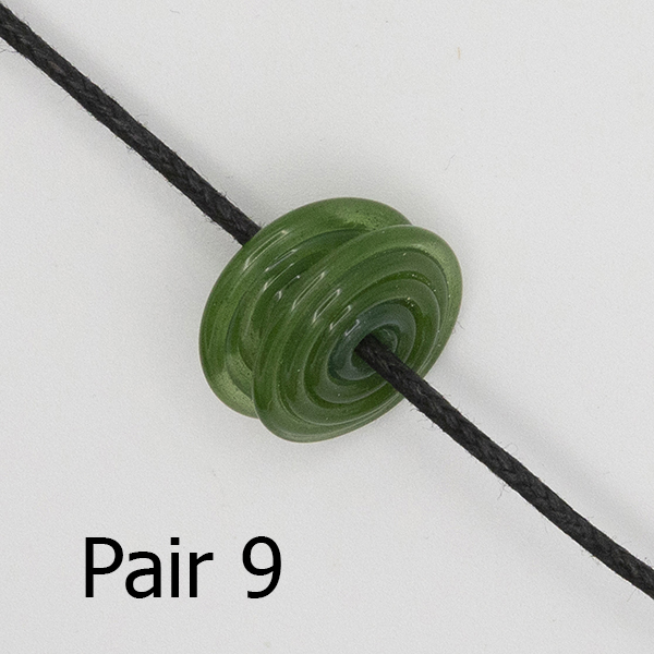 pair of spiral glass discs on a black cord