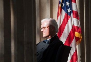 District Judge Gregory Van Tatenhove watches from the steps of the Old Capitol as a speech is given during the natrualization ceremony. © Bobby Ellis