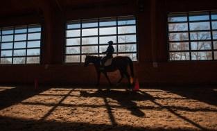 Casey Crockett rides a horse inside the arena at Stewart Home School. © Bobby Ellis