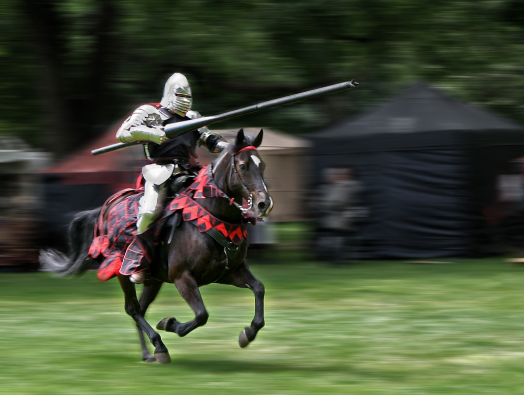 Armored rider with lance on horse. Motion blurred background.