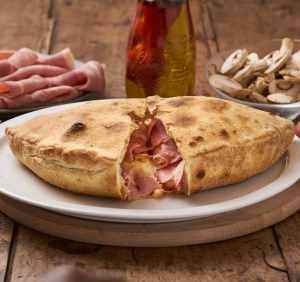 calzone reine sur une assiette poser sur une table en bois