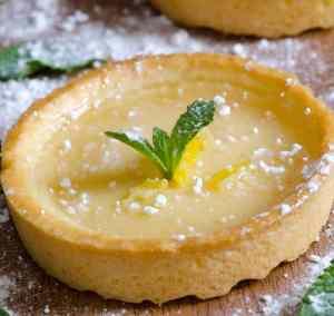 Tartelette citron posée sur un support en bois saupoudrer de sucre glace