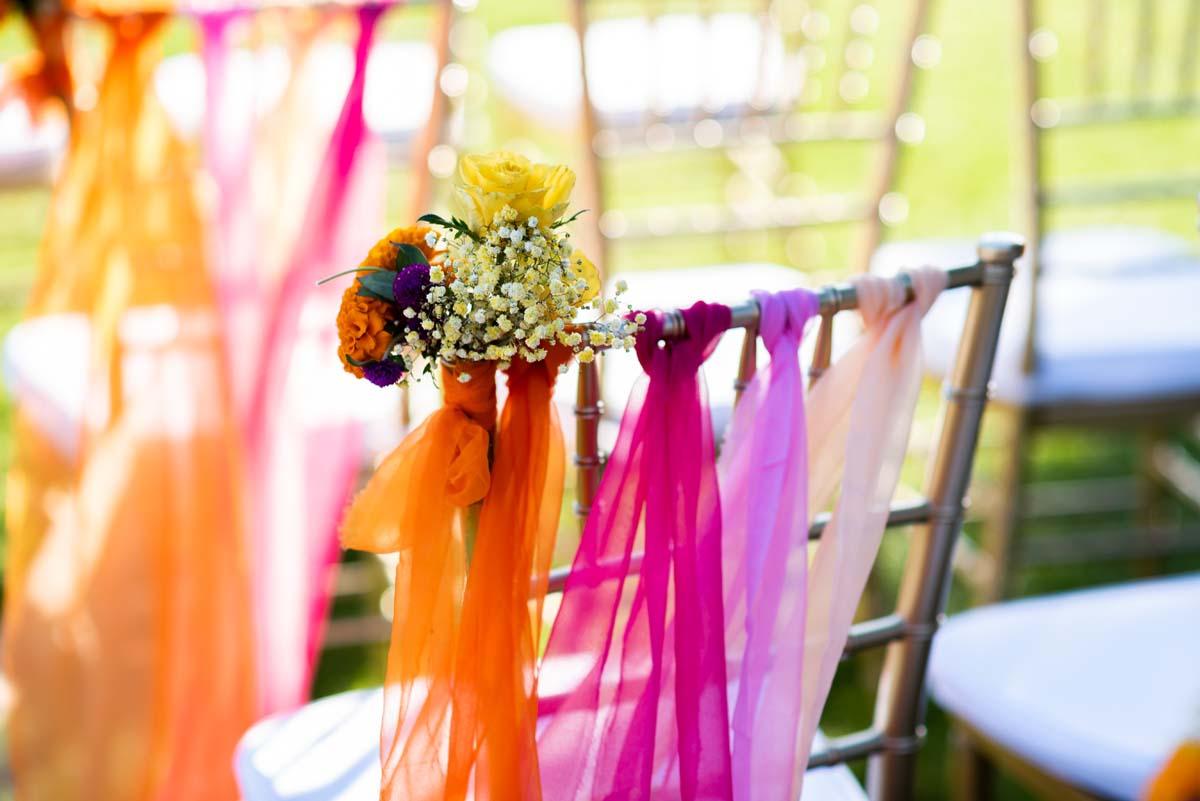 Silla para los invitados decorada con flores y telas de colores