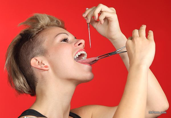 Woman piercing the tongue herself