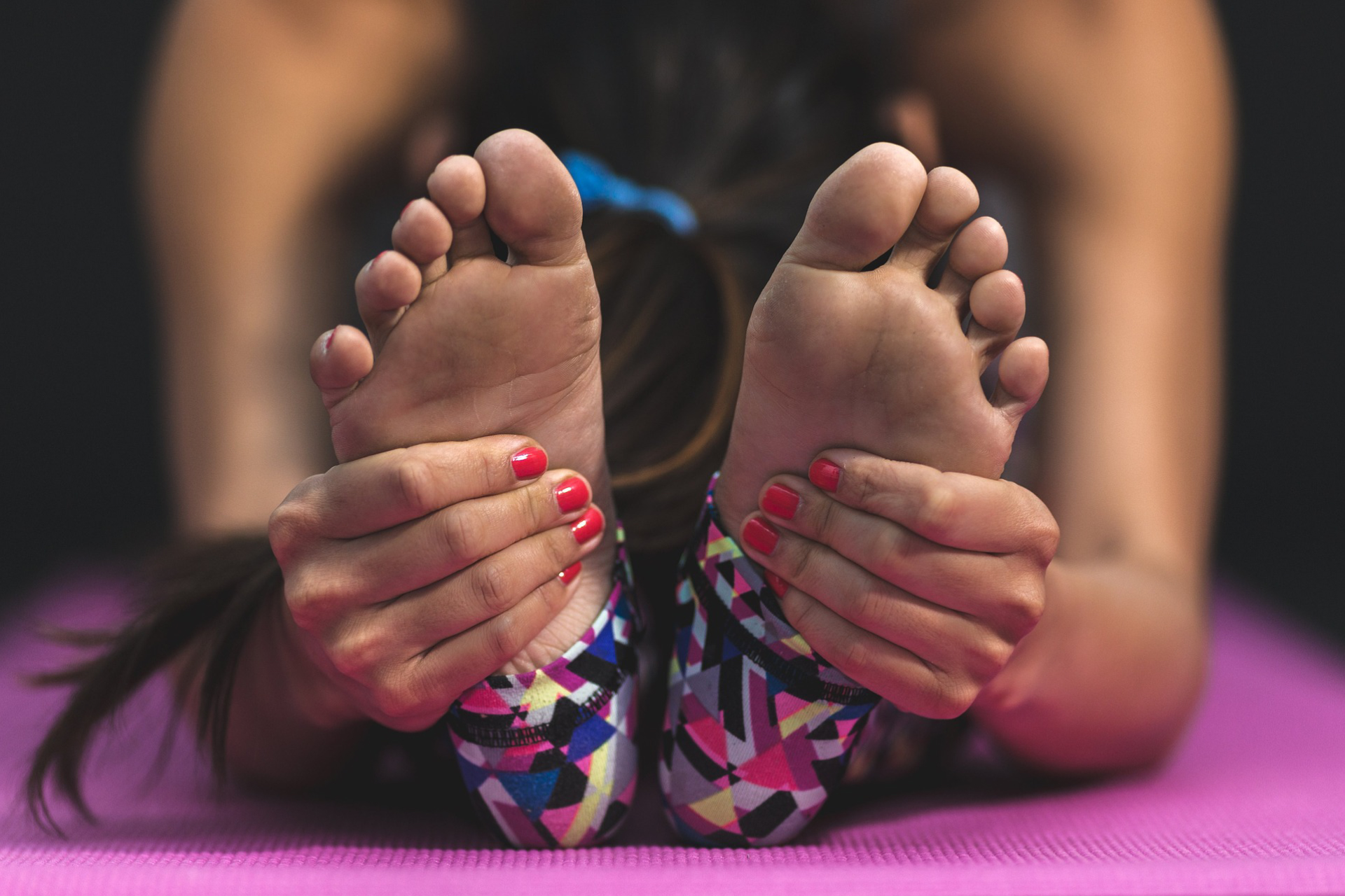woman holding feet; running injuries and how to overcome them