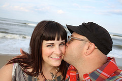 Image of me and my husband Jimmy (kissing my cheek) at the beach