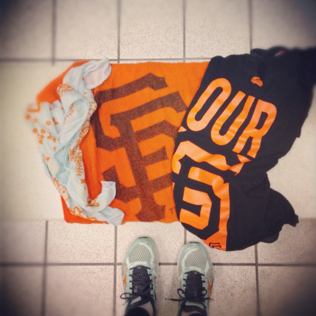 Image is from the perspective of gazing down at a tile floor. There is a pile of tshirts and a pair of running shoes.